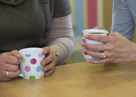 Close up of hands holding mugs with tea