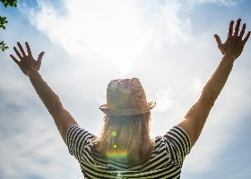 Person rising their hand up towards sunny sky